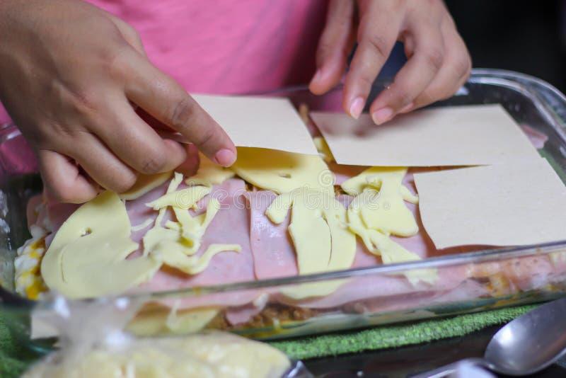 woman& x27; m?os de s que cozinham a lasanha das lasanhas, da massa, do presunto e do queijo foto de stock