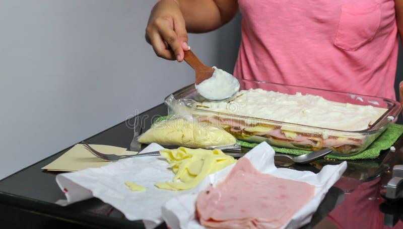 woman& x27; m?os de s que cozinham a lasanha das lasanhas, da massa, do presunto e do queijo fotos de stock