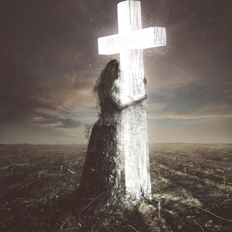 Woman made of dirt clings to the cross. A woman made out of sticks and dirt clings to the glowing cross stock photography
