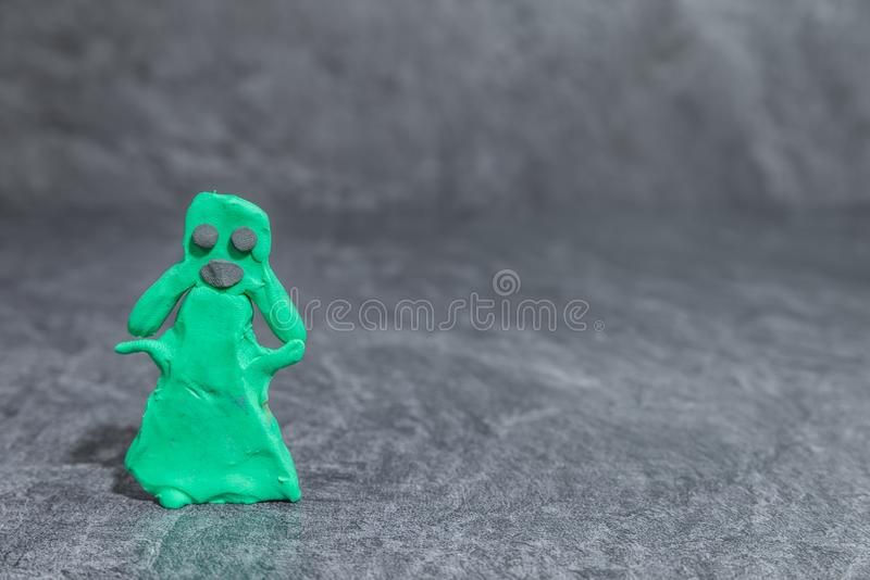 Woman made of green play dough in front of grey background.  royalty free stock images
