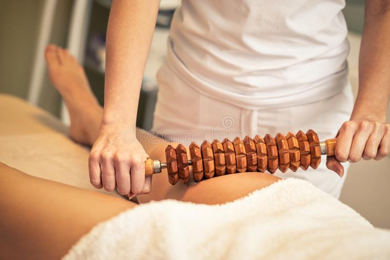 Maderotherapy anticellulite massage treatment at beauty spa salon. Woman on maderotherapy anticellulite massage treatment  of leg at beauty spa salon royalty free stock images