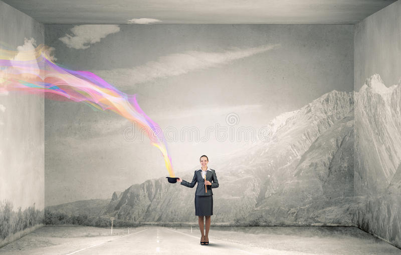 Woman magician with bowler hat. Attractive businesswoman with flute and bowler hat in hand royalty free stock image