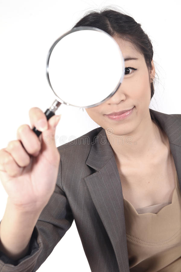 Woman and magnifying. Confident young woman looking through a magnifying glass isolated (blank space for text royalty free stock images