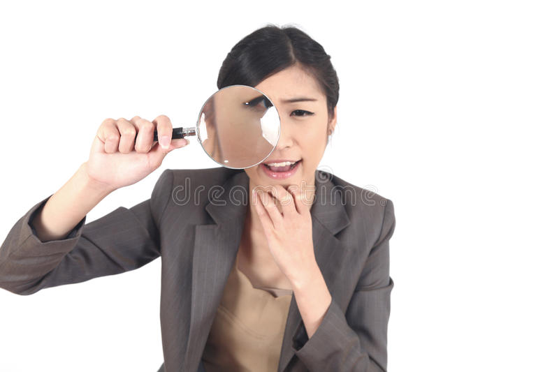 Woman and magnifying. Confident young woman looking through a magnifying glass isolated stock images