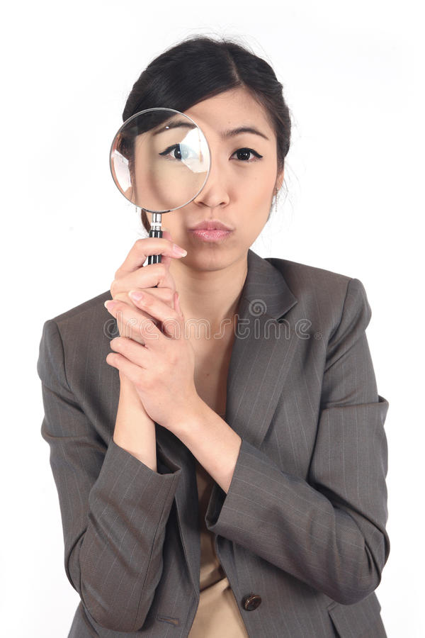 Woman and magnifying. Confident young woman looking through a magnifying glass isolated stock photos