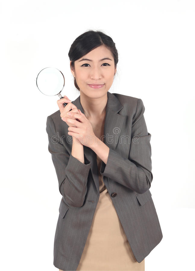 Woman and magnifying. Confident young woman looking through a magnifying glass isolated stock photography