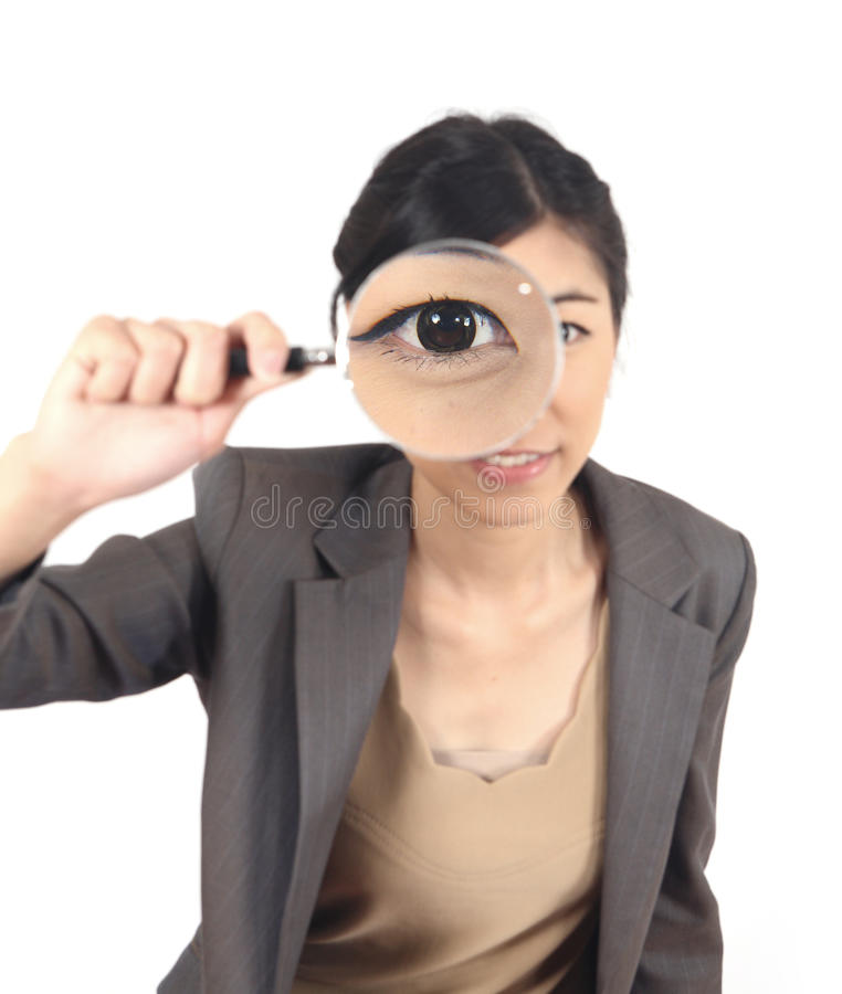 Woman and magnifying. Close-up young woman looking through a magnifying glass isolated stock photo