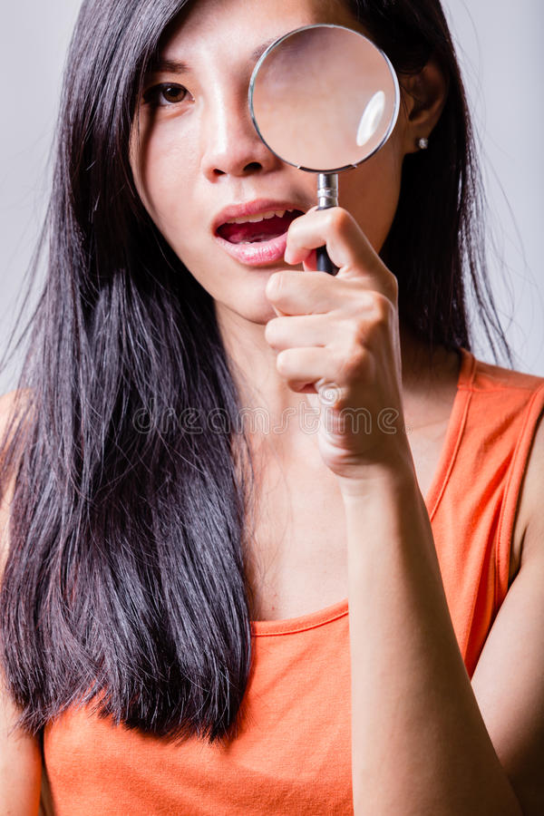 Woman with magnifying glass. Asian woman holding magnifying glass to eye stock image