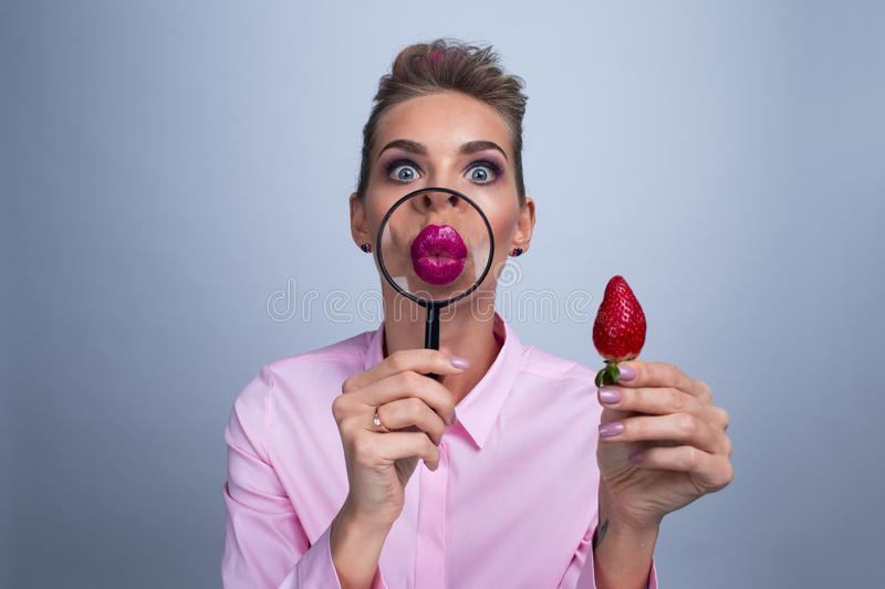 Woman with magnifying glass and strawberry. Pretty woman giving a kiss with magnifying glass and holding strawberry stock photography