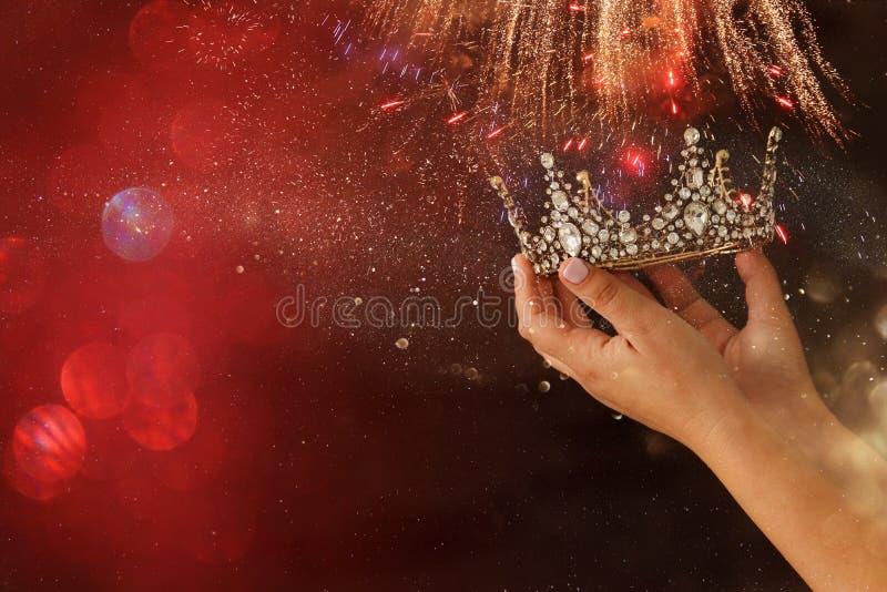 Woman& x27 ; main de s tenant une victoire de couronne en démonstration ou gagnant le premier endroit recouvrement de scintilleme photo stock