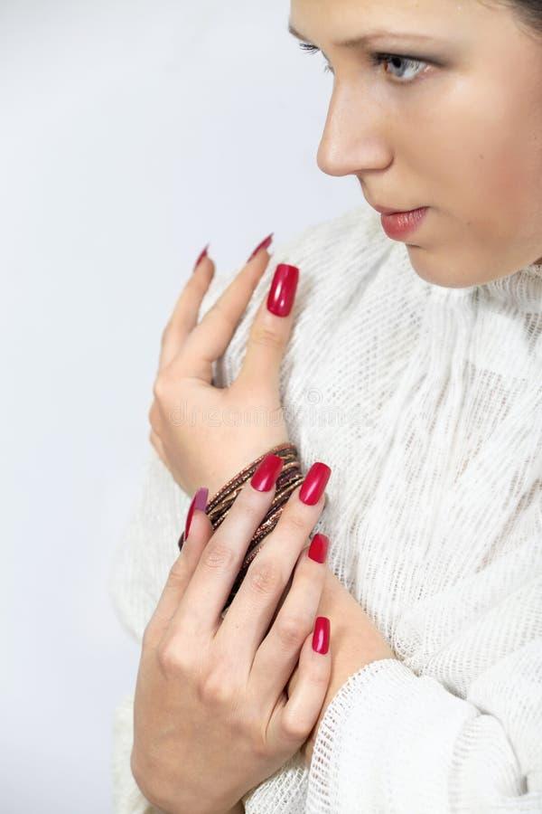 Woman& x27 ; mains de s avec les clous et les bracelets rouges photographie stock libre de droits