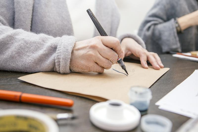 Woman make calligraphy writings, make art on a paper using pen b. Rush and sign pen. Adult, old hands of a calligrapher woman. Lifestyle image of a design royalty free stock photo