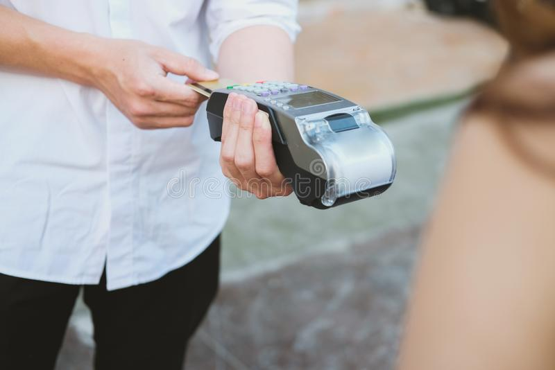 Woman make payment with credit card swipe through terminal. customer paying with EDC or swiping machine. buy & sell product or se. Woman make payment with credit stock photography