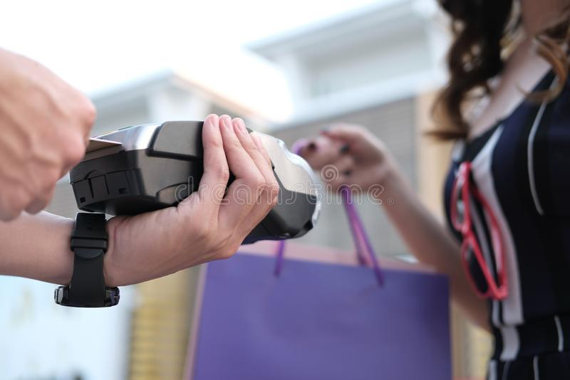 Woman make payment with credit card swipe through terminal. customer paying with EDC or swiping machine. buy & sell product or se. Woman make payment with credit royalty free stock photo
