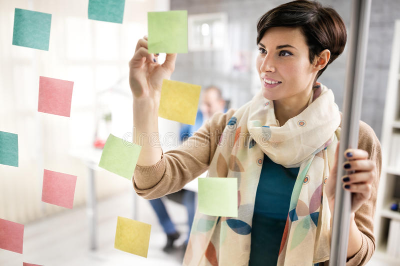Woman make scheme on sticky notes on glass board stock photos