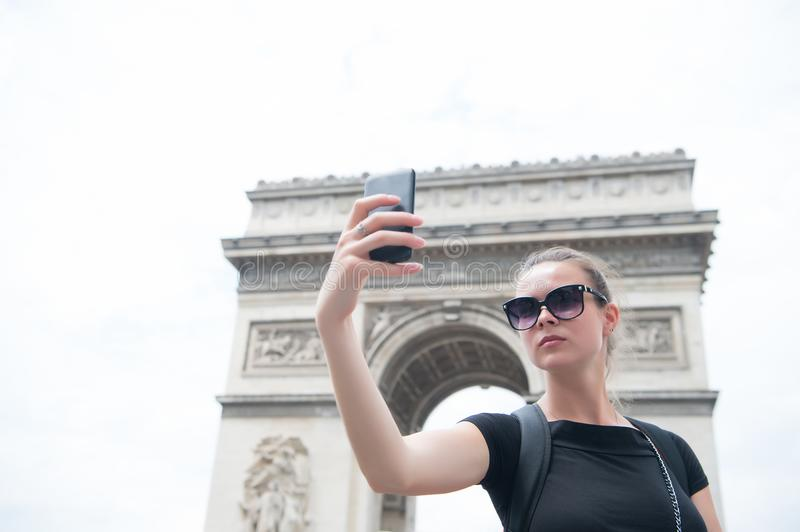 Woman make selfie with phone at arc de triomphe in paris, france. Woman with smartphone at arch monument. Vacation and sightseeing. In french capital. Girl with royalty free stock image