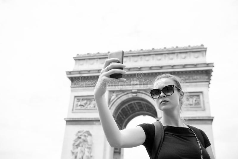 Woman make selfie with phone at arc de triomphe in paris, france. Woman with smartphone at arch monument. Vacation and. Sightseeing in french capital. Girl with royalty free stock images