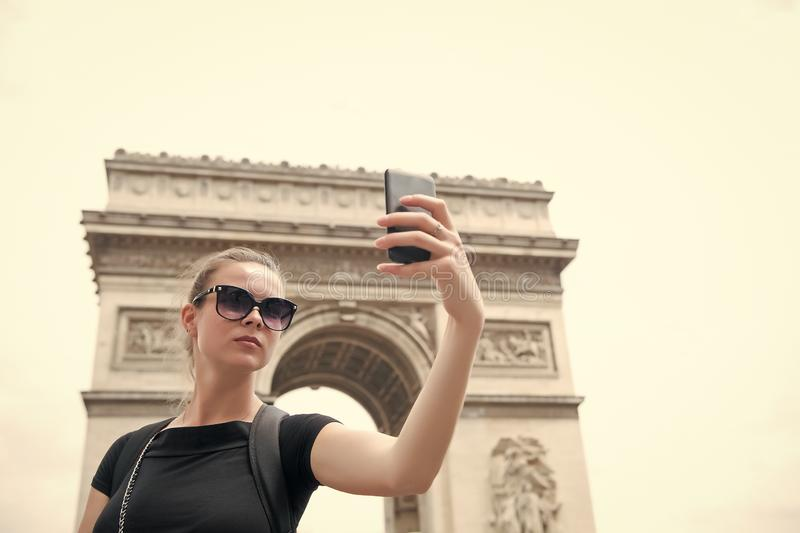 Woman make selfie with phone at arc de triomphe in paris, france. Woman with smartphone at arch monument. Vacation and stock photo