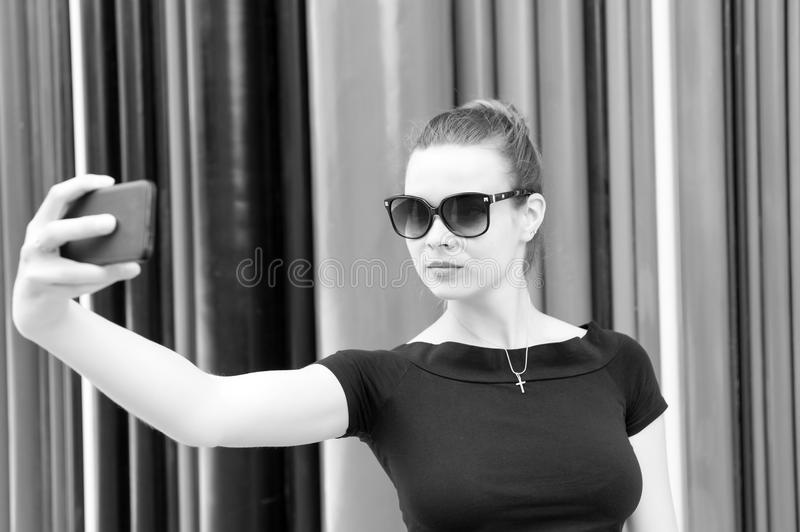 Woman make selfie with smartphone in paris, france. Woman with mobile phone on colorful background. Girl in sunglasses. With fashion look and sensual beauty stock photo