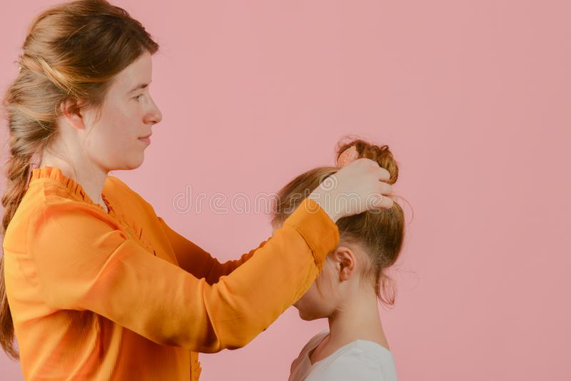 Woman make-up artist doing fashionable hairstyle to little girl stock image