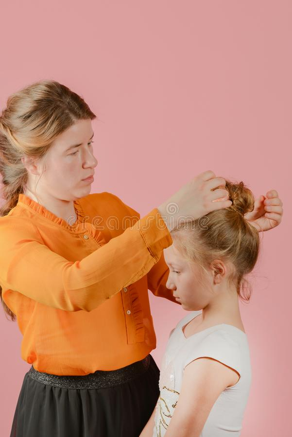 Woman make-up artist doing fashionable hairstyle to little girl royalty free stock image