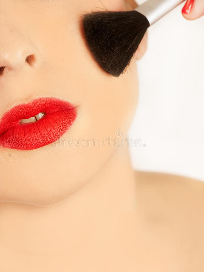 Woman with a make up brush and lips painted in red stock images