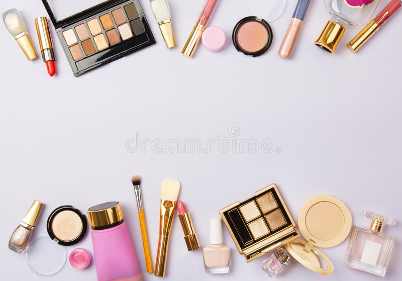 Woman make up cosmetics on purple. Decorative cosmetics: highlighter, concealer, rouge, palette with eye shadows and brushes for face make up, face sculpture royalty free stock image