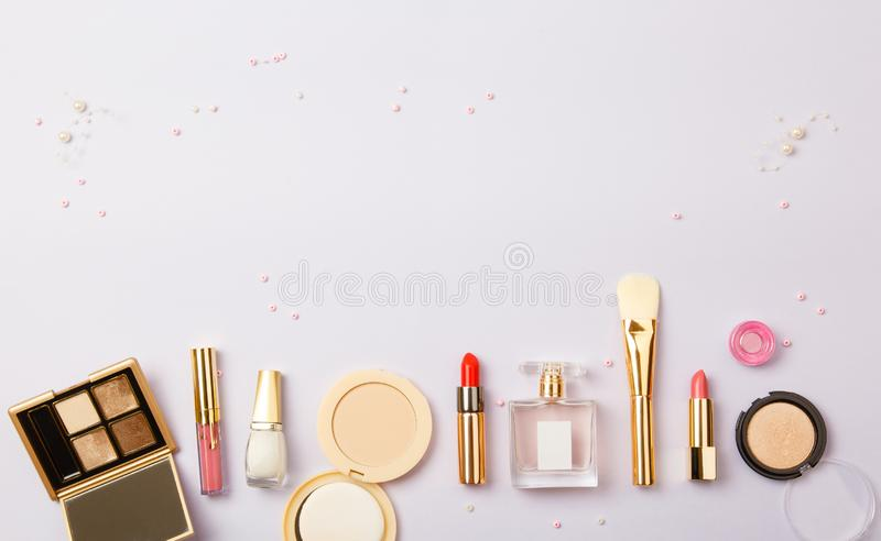 Woman make up cosmetics on purple. Decorative cosmetics: highlighter, concealer, rouge, palette with eye shadows and brushes for face make up, face sculpture royalty free stock photo