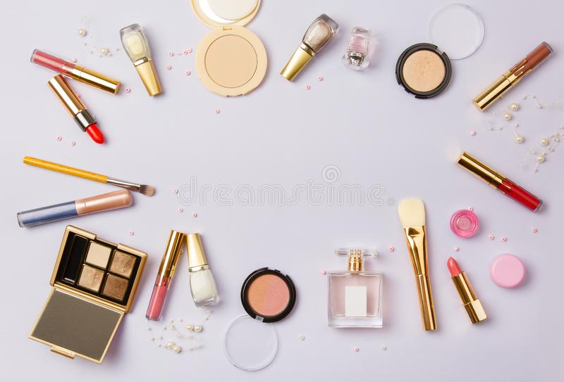 Woman make up cosmetics on purple. Decorative cosmetics: highlighter, concealer, rouge, palette with eye shadows and brushes for face make up, face sculpture stock image