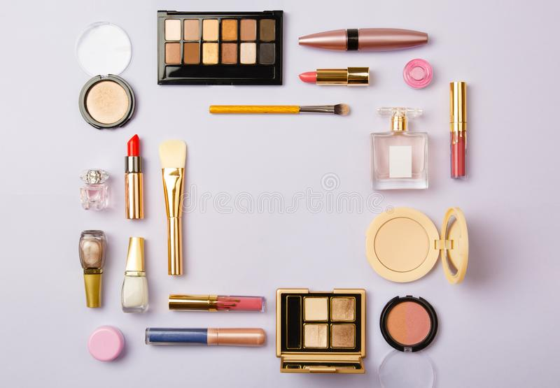 Woman make up cosmetics on purple. Decorative cosmetics: highlighter, concealer, rouge, palette with eye shadows and brushes for face make up, face sculpture stock photo