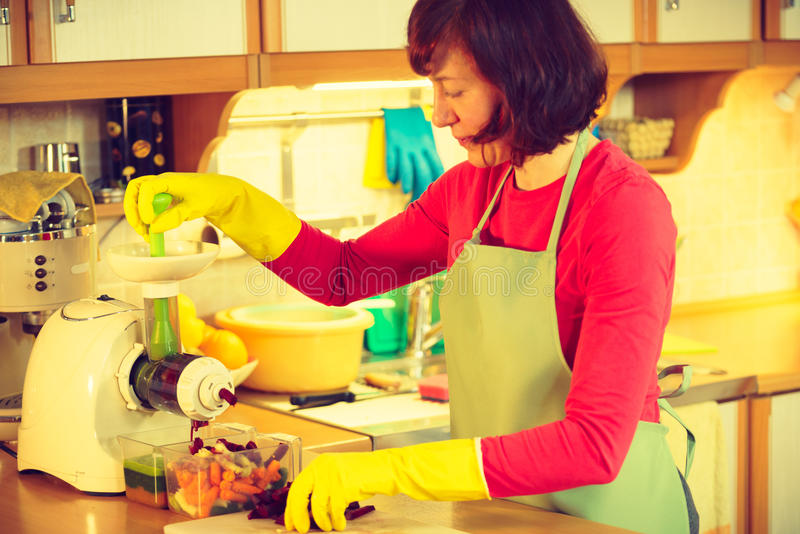Woman make vegetables juice in juicer machine stock photography