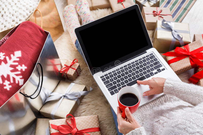 Woman makes christmas shopping online with laptop, above view stock photos