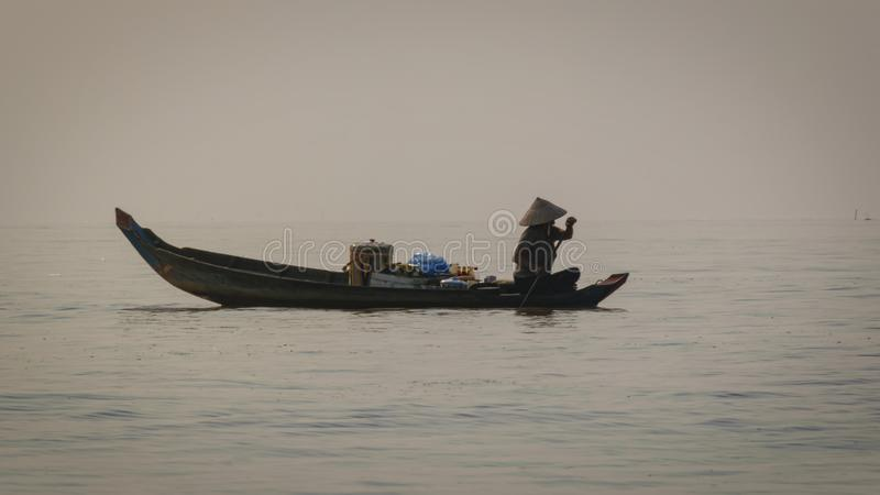 Woman makes her way across the lake in her floating kitchen boat. Most houses do not have cooking facilities so ladies like this. Cambodia, Tonle-Sap - March royalty free stock photos