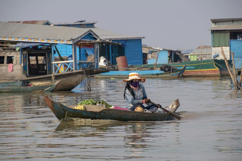 Woman makes her way across the lake in her floating market boat. Cambodia, Tonle-Sap - March 2016: Woman makes her way across the lake in her floating market stock images