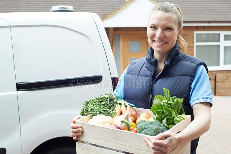 Woman Making Home Delivery Of Organic Vegetable Box stock images