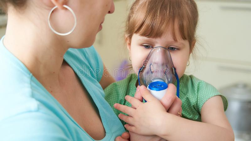 Woman makes inhalation to a child at home. brings the nebulizer mask to his face. inhales the vapor of the medication. the girl royalty free stock images