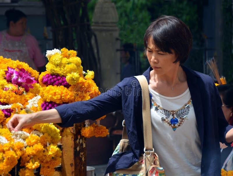 Woman Makes Offering at Erawan Hindu Shrine in Bangkok. royalty free stock images