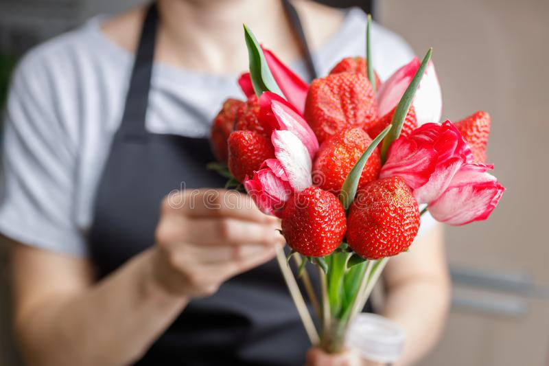 Woman makes an original bouquet of beautiful tulips and ripe strawberries stock photo