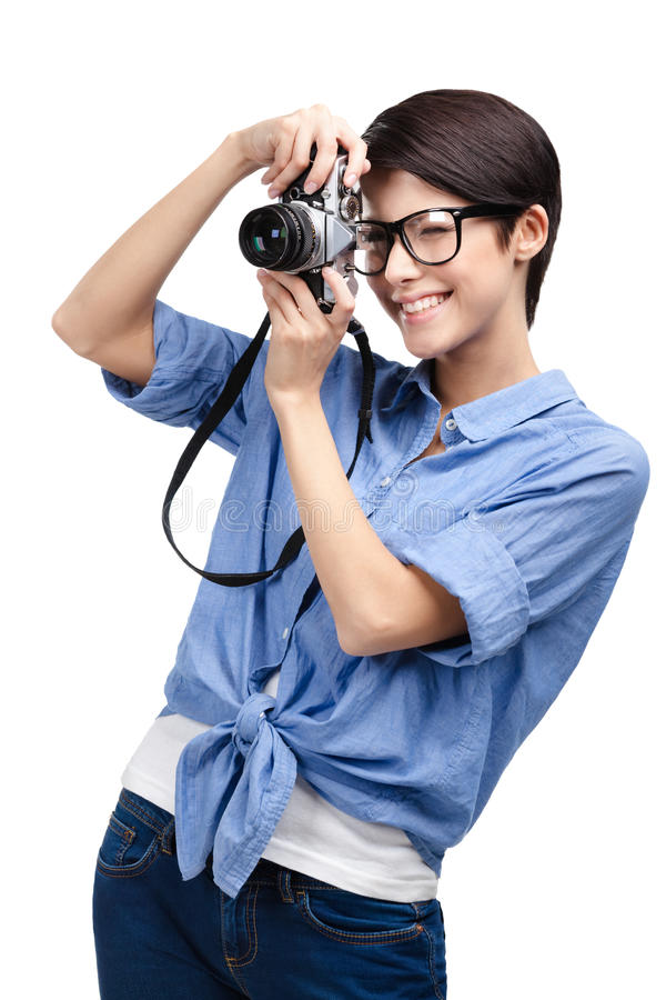 Woman makes photos with retro photographic camera. Woman in spectacles makes photos with retro photographic camera, isolated on white royalty free stock photos