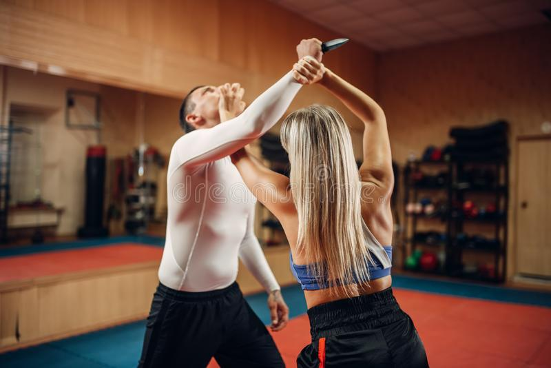 Woman makes punch to the throat, self-defense. Workout with male personal trainer, gym interior on background. Female person on training, self defense practice royalty free stock photo