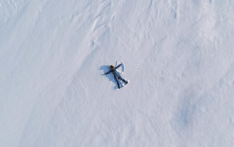 Woman makes snow angel laying in the snow. Top view. Aerial foto. Woman makes snow angel laying in the snow. Top view stock photo