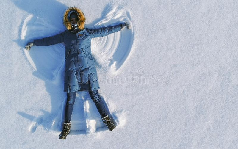 Woman makes snow angel laying in the snow. Top view. Aerial foto. Woman makes snow angel laying in the snow. Top view stock photos