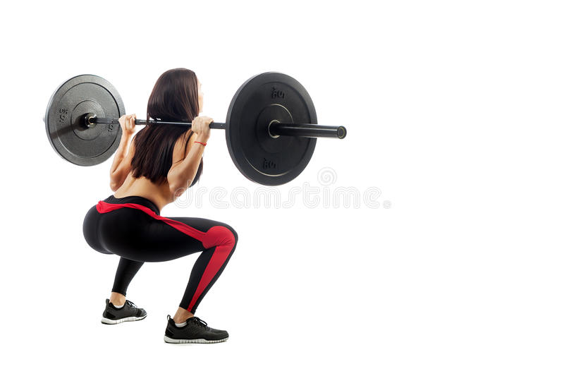 Woman makes a squat. Young sporty woman fitness model brunette doing a seated pad with a barbell on white isolated background, standing full squat stock photos
