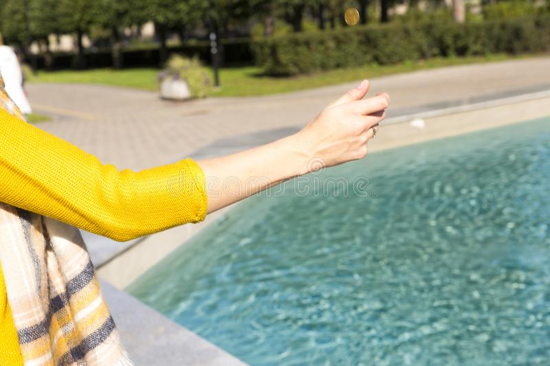 Woman makes a wish throwing coin into the fountain royalty free stock image