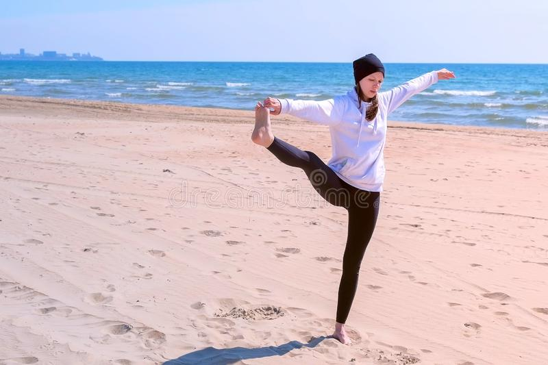 Woman makes yoga on sea beach raises her leg and holds it hand in balance pose. Woman practices yoga on sea beach on sand. She makes exercise raises her leg and stock images