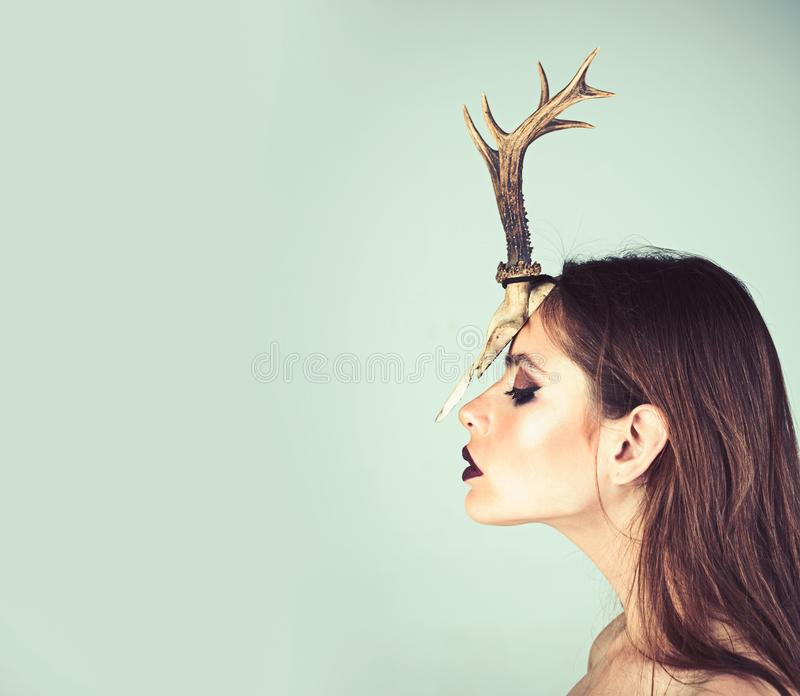 Woman with makeup and antlers. Fashion devil of mystic shaman girl with horns. Beauty look and cosmetics for skincare stock images