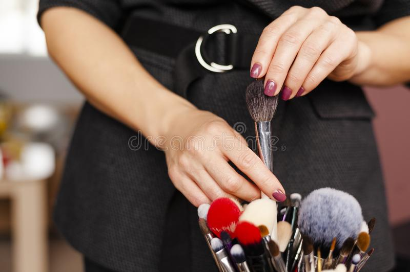 Woman makeup artist select and takes out brush from professional makeup brushes set. Closeup hands royalty free stock images