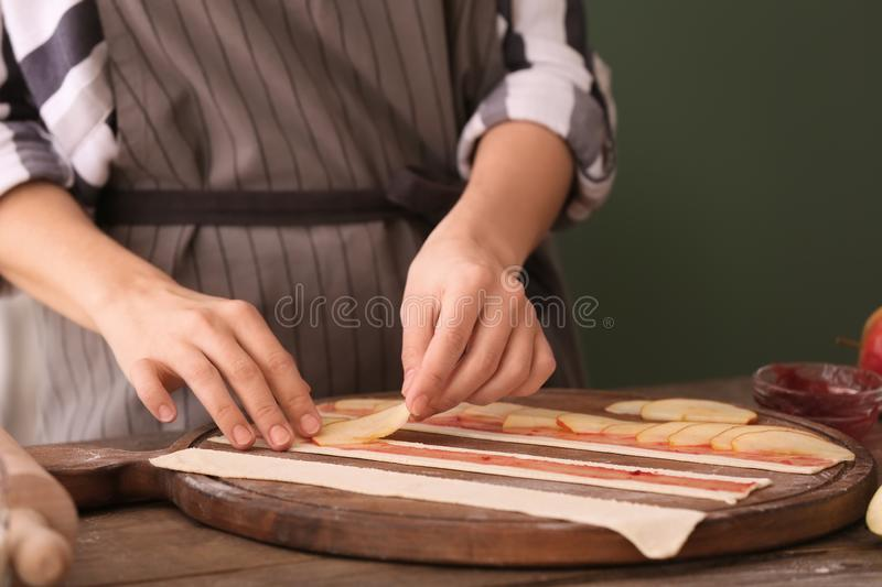 Woman making apple cakes in kitchen stock photos