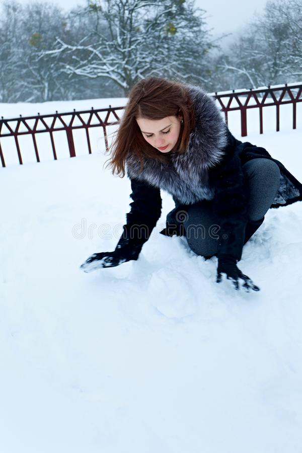 Woman is making a ball out of the snow royalty free stock photography