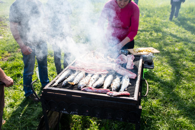 Woman making barbecue. A woman with friends standing next to a big grill barbecuing trout, pork and beef stock photos